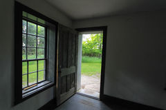Open Door To The Way Out. Empty room and window with open door leading outside. This is a historical building in a state park and not a privately owned residence Royalty Free Stock Photo
