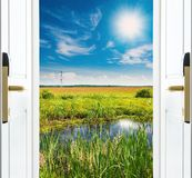 Open door with a view of green meadow illuminated by bright sunshine Royalty Free Stock Images