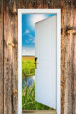Open door with a view of green meadow illuminated Stock Image