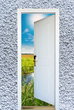 Open door with a view of green meadow illuminated Royalty Free Stock Photo