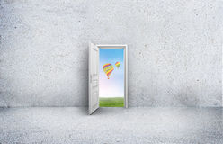 Open door with a view of the sky and hot air balloons. Concrete room Stock Photo