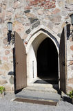 Open doors of medieval stone church Royalty Free Stock Photo