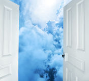 Open doors to dreamy blue clouds. Doors opening to dreamy fluffy clouds Royalty Free Stock Image