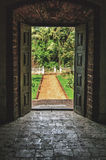 Open doors to the tropical garden at villa. Open doors to the tropical garden, the paved road to the door of the old Indian Villa.Vintage stone floor and walls royalty free stock photography