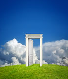 Open doorway in countryside. Conceptual image of open doorway on green grass with blue sky and cloudscape background with copy space Royalty Free Stock Photography