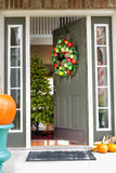 Open doorway to an inviting Christmas scene. With a colorful decorated wreath hanging on the wall and pumpkins on the porch in the foreground Royalty Free Stock Photos