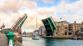 Open Drawbridge. Drawbridge (Bascule Bridge),  open to allow the passage of a tall masted yacht to leave the harbour, over which the bridge spans Stock Photos