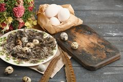 Open eco-friendly ceramic plate with feathers and quail eggs on rough dyed wooden background. Eggs For Easter. Boho stile royalty free stock photo