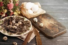 Open eco-friendly ceramic plate with feathers and quail eggs on rough dyed wooden background. Eggs For Easter. Boho stile stock image
