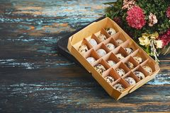 Open eco-friendly wooden box with quail eggs near dry flowers on rough dyed wooden background. Eggs For Easter. stock photos