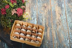 Open eco-friendly wooden box with quail eggs near dry flowers on rough dyed wooden background. Eggs For Easter. Boho stile stock images