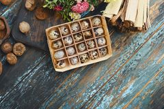 Open eco-friendly wooden box with quail eggs near dry flowers on rough dyed wooden background. Eggs For Easter. Boho stile royalty free stock image