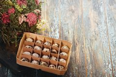 Open eco-friendly wooden box with quail eggs near dry flowers on rough dyed wooden background. Eggs For Easter. Boho stile stock photo