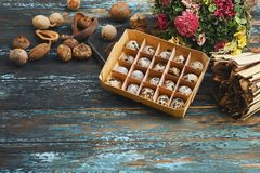 Open eco-friendly wooden box with quail eggs near dry flowers on rough dyed wooden background. Eggs For Easter. Boho stile stock photography