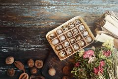 Open eco-friendly wooden box with quail eggs near dry flowers on rough dyed wooden background. Eggs For Easter. Boho stile stock photos