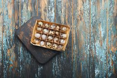 Open eco-friendly wooden box with quail eggs on rough dyed wooden background. Eggs For Easter. Boho stile royalty free stock image