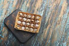 Open eco-friendly wooden box with quail eggs on rough dyed wooden background. Eggs For Easter. Boho stile royalty free stock images