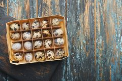 Open eco-friendly wooden box with quail eggs on rough dyed wooden background. Eggs For Easter. Boho stile stock photos