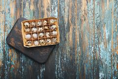 Open eco-friendly wooden box with quail eggs on rough dyed wooden background. Eggs For Easter. Boho stile stock photography