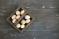 Open eco-friendly wooden box with turkey eggs. Rough dyed wooden background. Eggs For Easter royalty free stock images