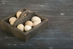Open eco-friendly wooden box with turkey eggs. Rough dyed wooden background. Eggs For Easter royalty free stock photos