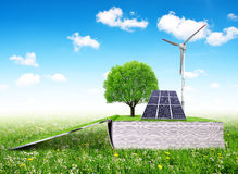 Open ecological book with solar panel and wind turbine Royalty Free Stock Photo
