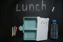 Open een lege lunchdoos met een snoepje weinig gezicht en een fles water op een zwarte achtergrond met kleurrijke kleurpotloden e royalty-vrije stock foto