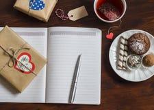 Open een schone lege Blocnote, eigengemaakte giften van de Valentijnskaartendag, een Kop thee en snoepjes op houten bruine lijst stock foto's