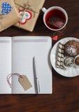 Open een schone lege Blocnote, eigengemaakte giften van de Valentijnskaartendag, een Kop thee en snoepjes op houten bruine lijst royalty-vrije stock afbeeldingen