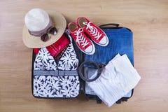 Open embaló la maleta con la ropa y los accesorios femeninos, bañador, sombrero, gafas de sol, zapatillas de deporte, camisa blan Fotografía de archivo libre de regalías