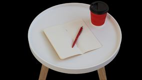 Open empty blank note paper with red pen, red cardboard cup of coffee to go on white round journal wood table isolated. On black background stock photography