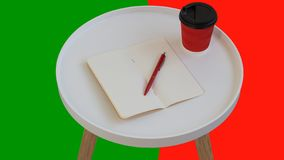 Open empty blank note paper with red pen, red cardboard cup of coffee to go on white round journal wood table isolated. On green and red background royalty free stock photography
