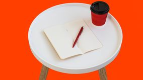 Open empty blank note paper with red pen, red cardboard cup of coffee to go on white round journal wood table isolated. On orange background stock photography