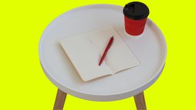 Open empty blank note paper with red pen, red cardboard cup of coffee to go on white round journal wood table isolated. On yellow background royalty free stock images
