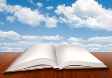 Open empty book with blank pages and blue sky Royalty Free Stock Images