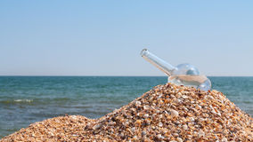The open empty bottle lay on a hill of sand Stock Images