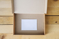 Open empty box with white card inside. Open, empty box, front view,  on natural wooden table with white card inside Royalty Free Stock Photography
