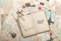 Open empty diary book, old letters, french postcards. Nostalgic vintage scrapbook background with sample text Journal intime (Diary) in french Stock Photography