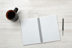 Open empty notebook and black pen on it with cup of hot coffee Stock Photography