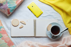 Open empty notebook with cup of coffee and cell phone in a bed Royalty Free Stock Images