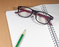 Open empty notebook with green pencil, eyeglasses and lined page Stock Photo