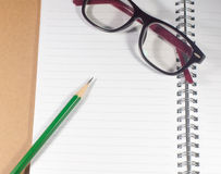 Open empty notebook with green pencil, eyeglasses and lined page Stock Image