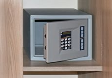Open empty safe. Empty hotel safe with open door and digital passcode on wooden shelf stock photos