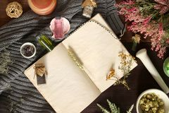 An open empty vintage notebook surrounded by herbs, alchemy appliances, potions and ingredients lies on a dark wooden table. Magic stock images