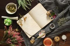 An open empty vintage notebook surrounded by herbs, alchemy appliances, potions and ingredients lies on a dark wooden table. Magic. Alchemy and occultism. Flat stock photography