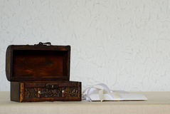 Open empty wooden box, white postcard with ribbons on a white background Royalty Free Stock Photos