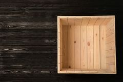 Open empty wooden crate on dark background, top view. With space for text royalty free stock images