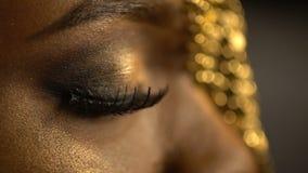 Open en gesloten ogen met bronsoogschaduw en kattenogen op het gezicht die van Afrikaans meisje gouden juwelen op haar dragen stock video