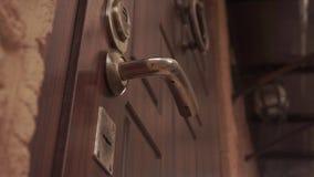 Open en sluit de deur met een zeer belangrijk deurslot onder het deurhandvat stock video
