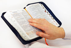 Open English Bible in hand on white Royalty Free Stock Photography